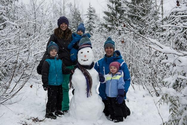 Porträt der glücklichen familie, die durch schneemann steht