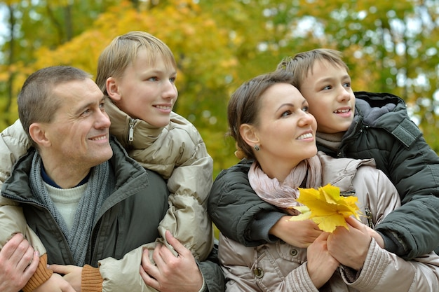 Porträt der glücklichen familie, die im herbstpark sich entspannt