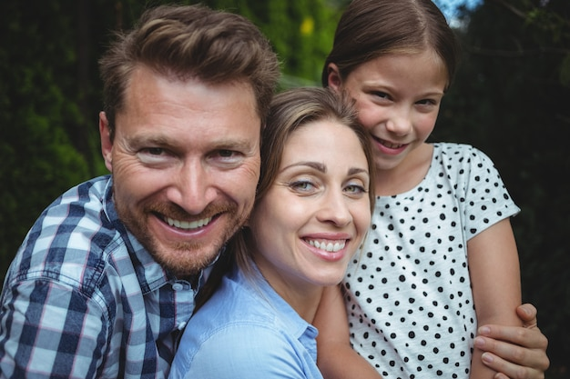 Porträt der glücklichen familie, die im park lächelt