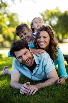 Porträt der glücklichen familie, die im park spielt