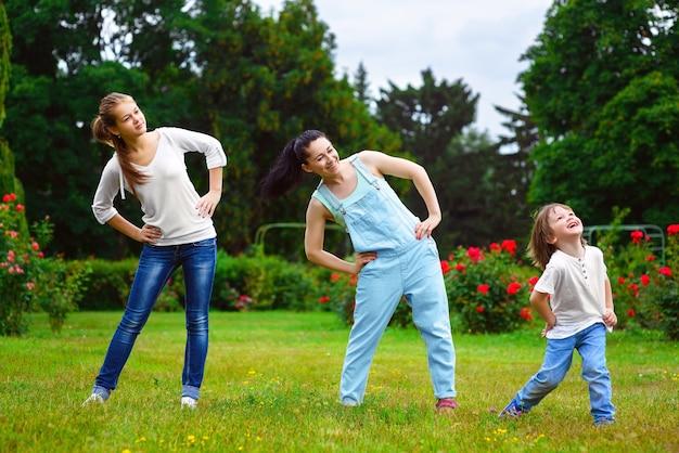 Porträt der glücklichen familie, die körperliche bewegung oder fitness im park tut.
