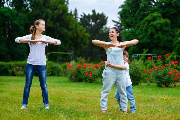 Porträt der glücklichen familie, die körperliche bewegung oder fitness im park tut