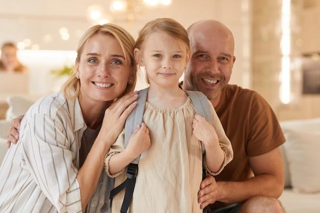 Porträt der glücklichen familie, die lächelt, während sie mit dem niedlichen kleinen mädchen posiert, das rucksack trägt