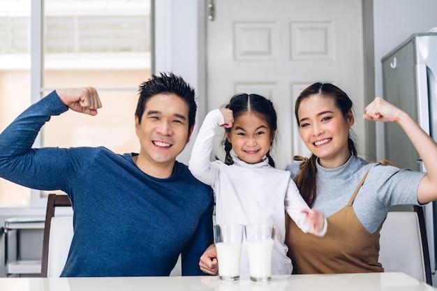 Porträt der glücklichen familie, die milch aufwirft und trinkt