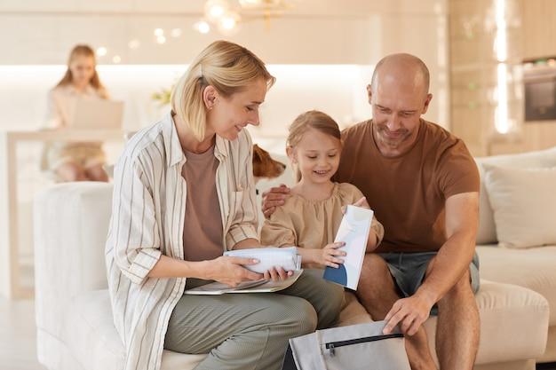 Porträt der glücklichen familie, die niedliches kleines mädchen hilft, rucksack für schule zu packen, während auf couch zu hause sitzen sitzt