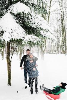 Porträt der glücklichen familie, die schnee im winterpark weht. familienspiel auf schneebedecktem winterspaziergang in der natur.
