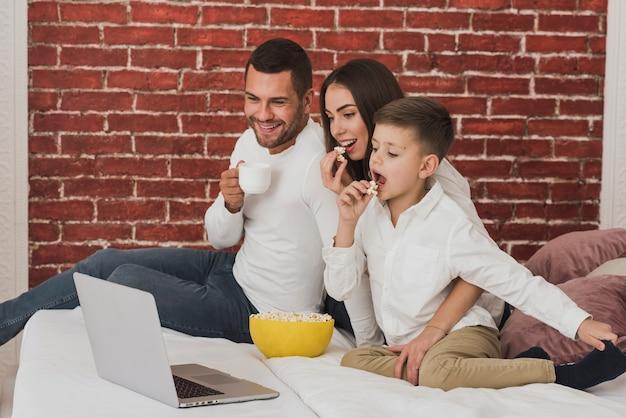 Porträt der glücklichen familie einen film aufpassend