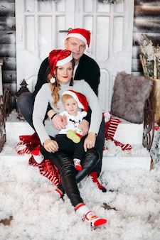 Porträt der glücklichen familie in den roten weihnachtsmützen, die auf der treppe mit schnee unter den füßen umarmt sitzen