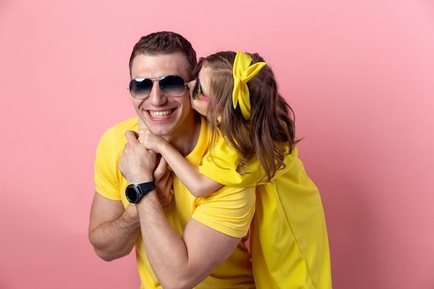 Porträt der glücklichen familie in der gelben kleidung mit sonnenbrille