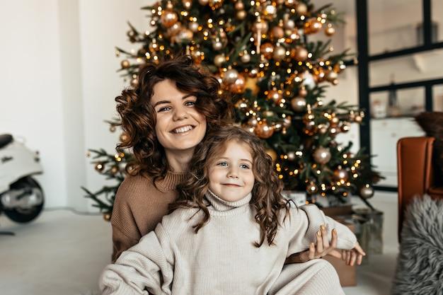 Porträt der glücklichen familie in gestrickten kleidern, die weihnachten und neujahr feiern