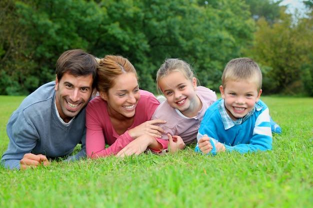 Porträt der glücklichen familie liegend im gras