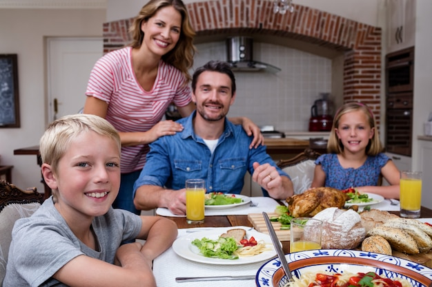 Porträt der glücklichen familie mahlzeit in der küche habend