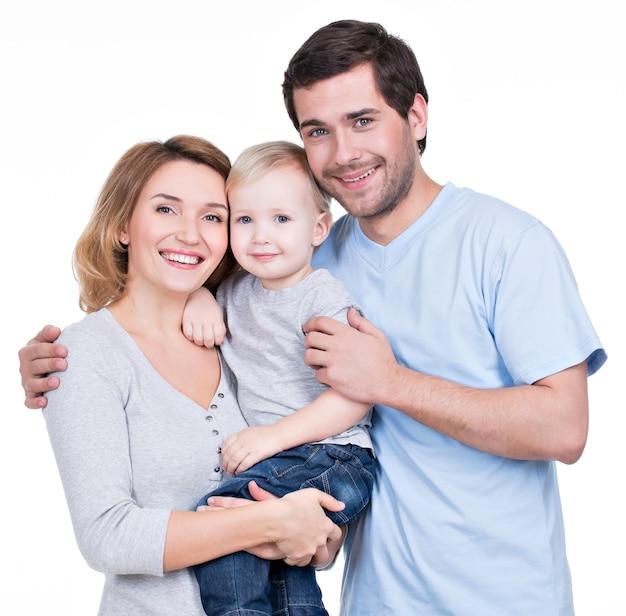 Porträt der glücklichen familie mit dem kleinen kind, das kamera betrachtet - lokalisiert
