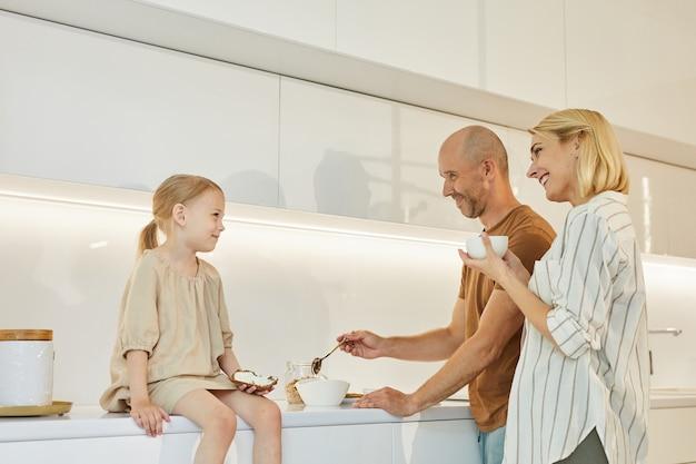 Porträt der glücklichen familie mit dem niedlichen kleinen mädchen, das frühstück zusammen kocht, während im innenraum der küche zu hause steht