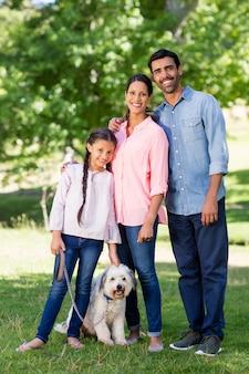 Porträt der glücklichen familie mit ihrem haustierhund, der im park steht