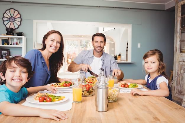Porträt der glücklichen familie mit lebensmittel auf speisetische
