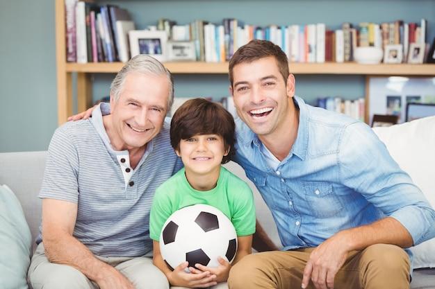 Porträt der glücklichen familie mit mehreren generationen mit fußball