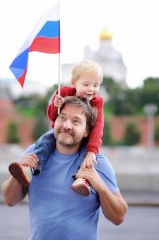 Porträt der glücklichen familie mit russischer flagge mit moskau der kreml auf hintergrund