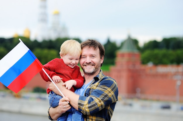 Porträt der glücklichen familie mit russischer flagge mit moskau der kreml