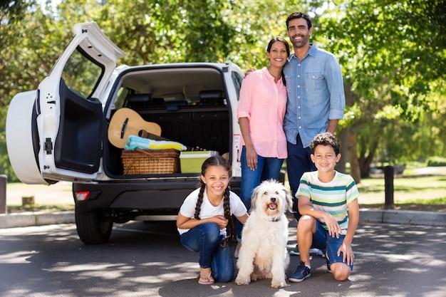 Porträt der glücklichen familie neben ihrem auto, das spaß hat