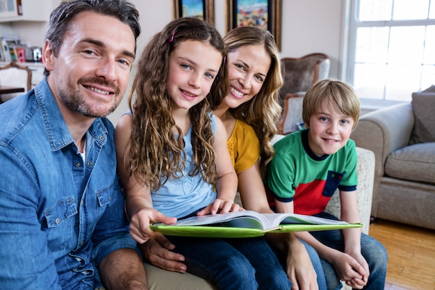 Porträt der glücklichen familie sitzend auf sofa mit fotoalbum
