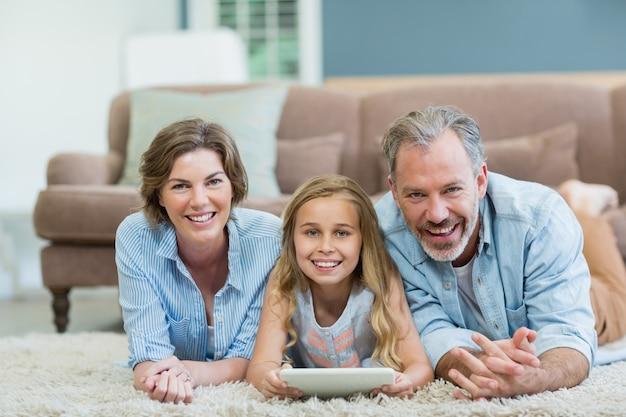 Porträt der glücklichen familie unter verwendung der digitalen tablette beim liegen auf dem boden im wohnzimmer