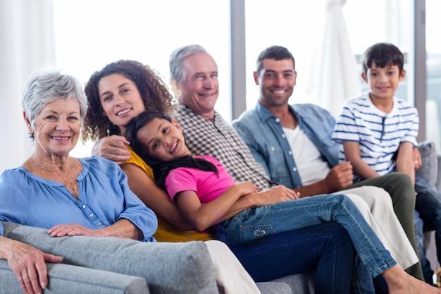 Porträt der glücklichen familie zusammen sitzend auf sofa