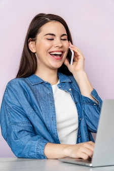 Porträt der glücklichen frau, die am telefon spricht und laptop verwendet