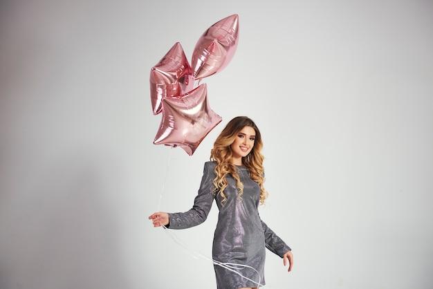 Porträt der glücklichen frau, die bündel der luftballons hält