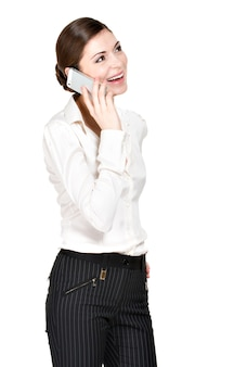 Porträt der glücklichen frau, die durch handy im weißen hemd anruft - lokalisiert auf weiß.