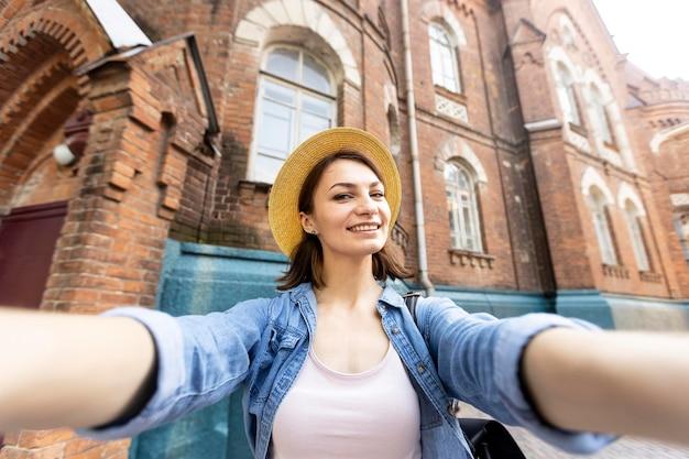Porträt der glücklichen frau, die ein selfie im freien nimmt