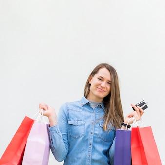 Porträt der glücklichen frau, die einkaufstaschen trägt