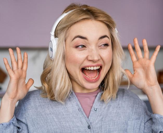 Porträt der glücklichen frau, die lacht und musik über kopfhörer hört