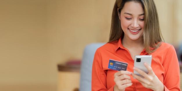 Porträt der glücklichen frau, die smartphone mit kreditkarte und lächelndem gesicht im kreativen büro oder im café am einkaufszentrum hält