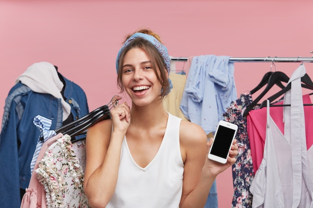 Porträt der glücklichen frau, die weißes t-shirt trägt, kleiderbügel mit modischer kleidung und smartphone in händen hält, freude beim einkaufen hat und leeren bildschirm ihres handys demonstriert