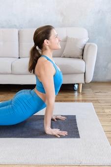 Porträt der glücklichen frau, die yoga zu hause auf matte im raum tut