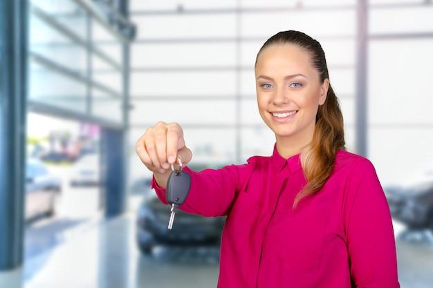 Porträt der glücklichen frau einen autoschlüssel halten