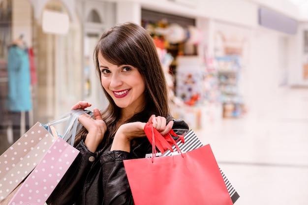 Porträt der glücklichen frau einkaufstaschen halten
