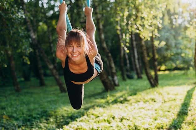 Porträt der glücklichen frau fliegenyoga am baum tuend und die kamera betrachtend.