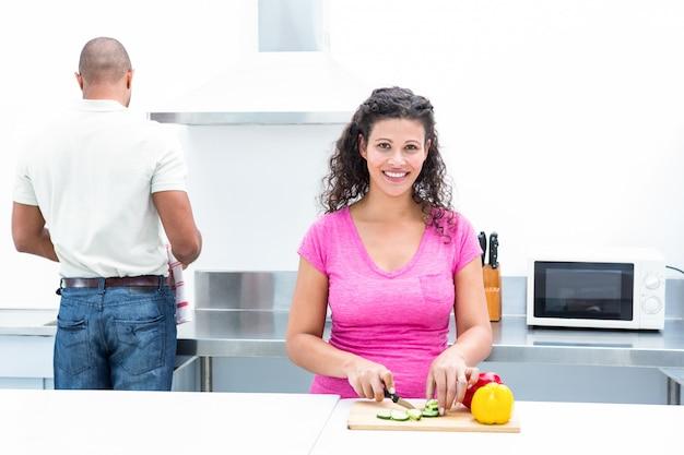Porträt der glücklichen frau gemüse hackend während ehemann, der zu hause in der küche arbeitet
