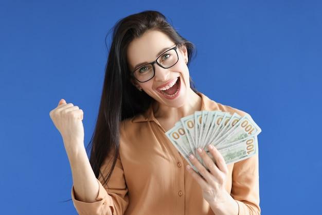 Porträt der glücklichen frau in den gläsern mit geld in ihren händen