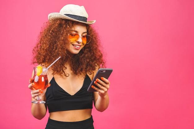 Porträt der glücklichen frau in der sonnenbrille unter verwendung des smartphones und des haltens des cocktails isoliert