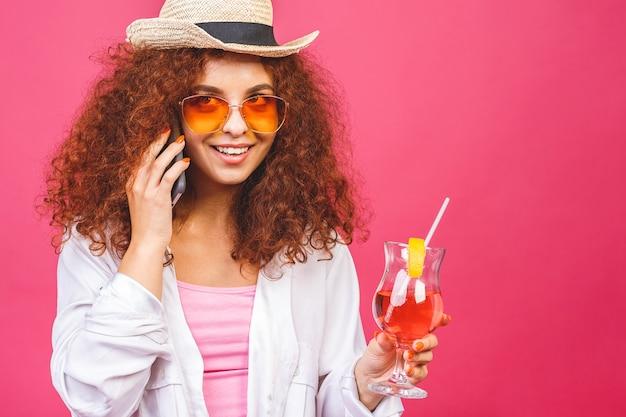 Porträt der glücklichen frau in der sonnenbrille unter verwendung des smartphones und des haltens des cocktails lokalisiert auf rosa hintergrund