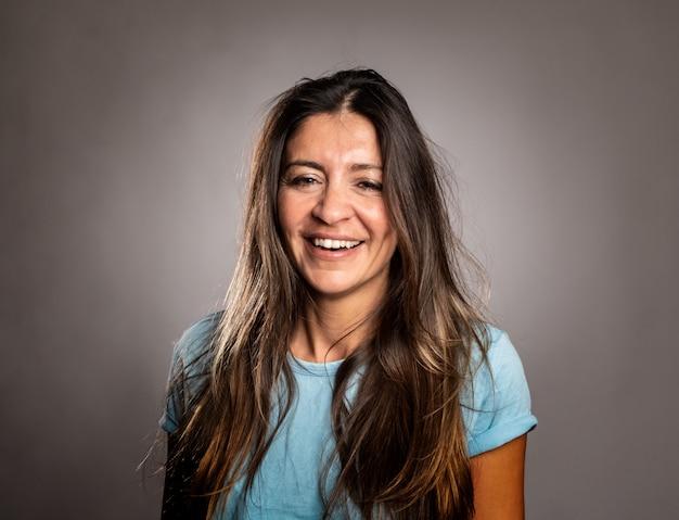 Porträt der glücklichen frau lächelnd auf grau