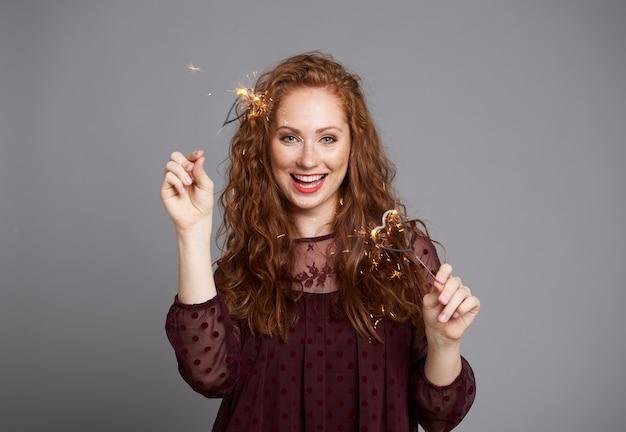 Porträt der glücklichen frau mit brennenden wunderkerzen bei studioaufnahme