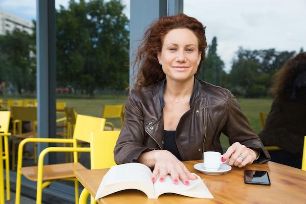 Porträt der glücklichen frau mit espresso und gutem buch am café
