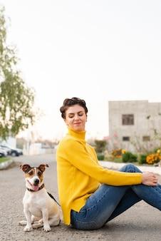 Porträt der glücklichen frau mit ihrem hund draußen