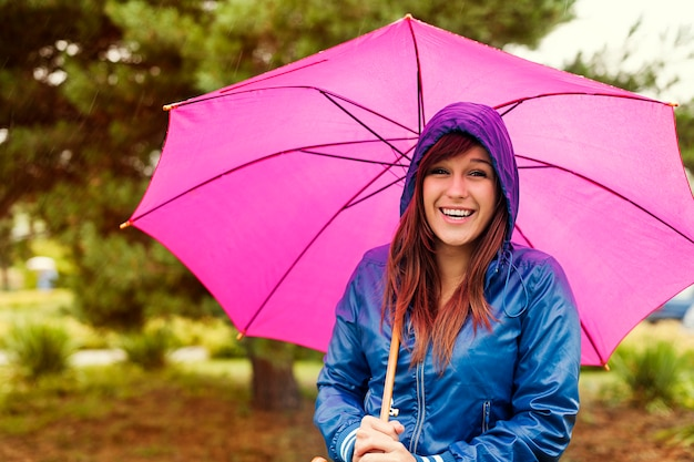 Porträt der glücklichen frau mit regenschirm