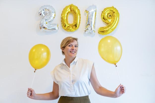 Porträt der glücklichen frau stehend mit ballonen unter zeichen 2019