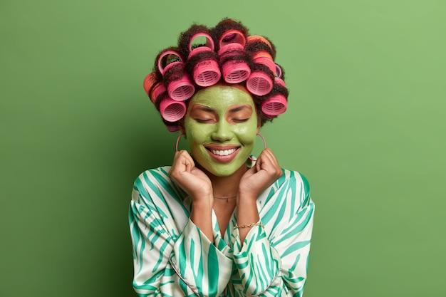 Porträt der glücklichen frau steht mit geschlossenen augen und zahnigem lächeln, geballten fäusten nahe gesicht, trägt schönheitsmaske für hautpflege und verjüngung auf, macht perfekte lockige frisur, isoliert auf grüner wand